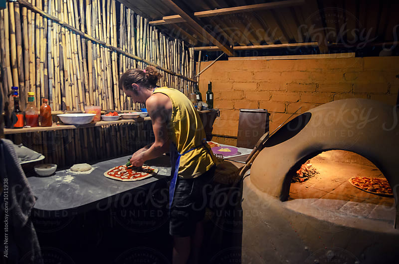Man making pizza next to the firewood oven in the night at rustic kitchen by Alice Nerr for Stocksy United