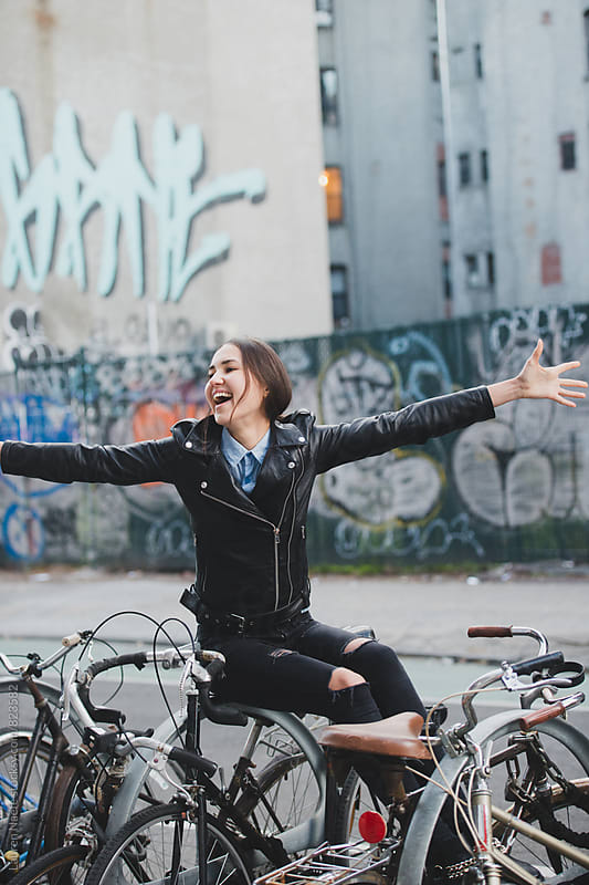 Free-spirited young woman sitting on bike rack by Lauren Naefe for Stocksy United
