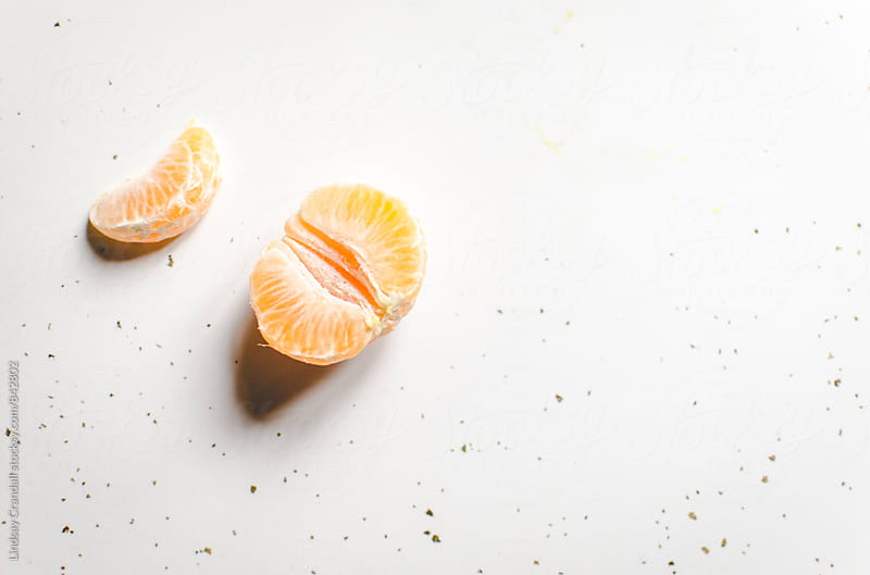 Small peeled orange on white counter by Lindsay Crandall for Stocksy United