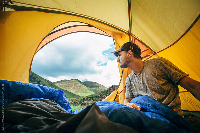 Man camping in a tent looking at a mountainous view by Micky Wiswedel for Stocksy United