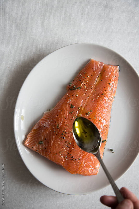 Woman prepare a salmon fillet to be cooked by Davide Illini for Stocksy United