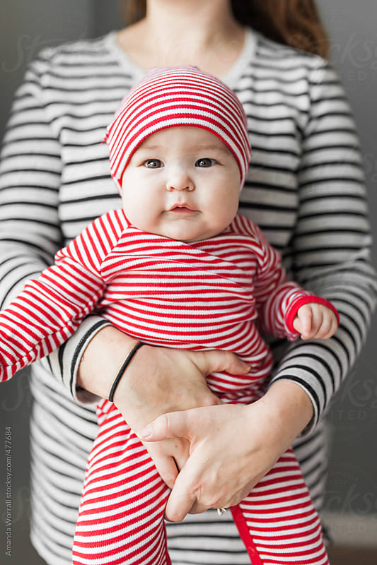 Mother holding cute, chubby baby wearing striped Christmas pajamas  by Amanda Worrall for Stocksy United