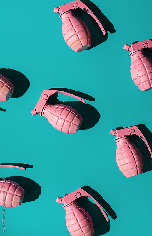 Pink hand grenades on blue background. by Marko Milanovic for Stocksy United