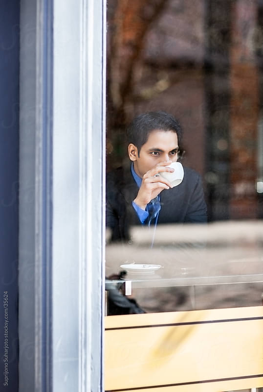 Indian businessman drinking coffee in a cafe by Suprijono Suharjoto for Stocksy United