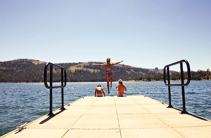 Woman jumping off the dock with her arms out -  into a lake between two girls by Carolyn Lagattuta for Stocksy United