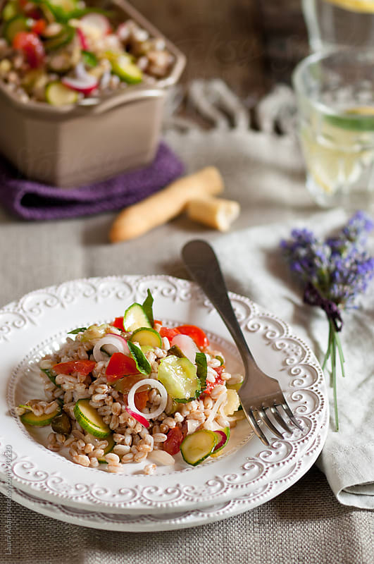 spelt salad with fresh vegetables served on a white decorated dish by Laura Adani for Stocksy United