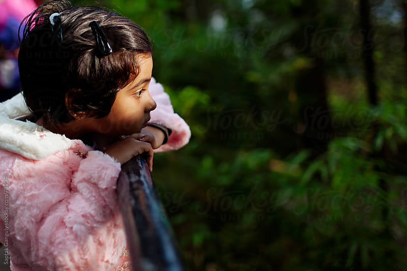 Little girl in a pensive mood resting her head on a railing by Saptak Ganguly for Stocksy United