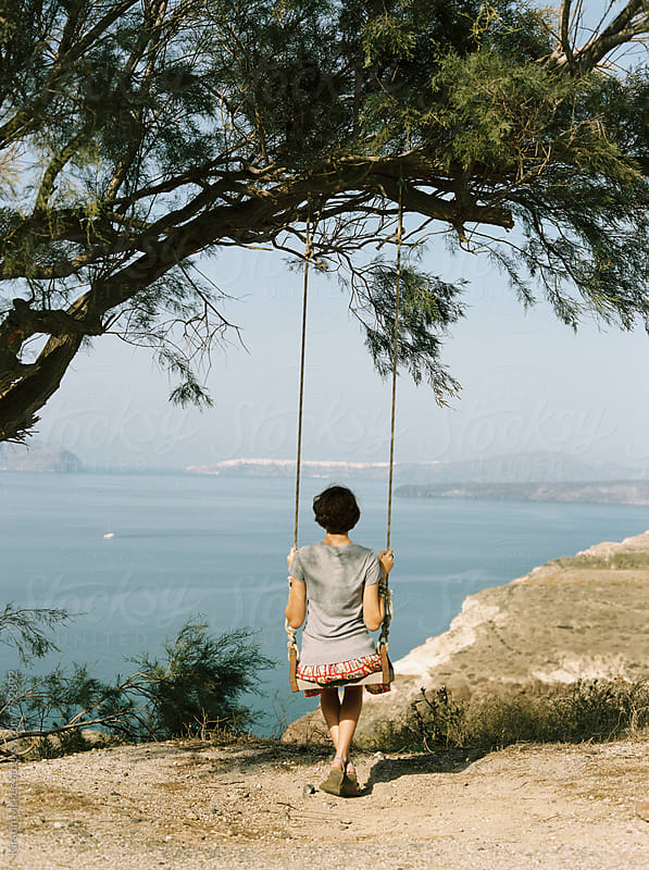 Rear view of girl on swing with view of sea by Kirstin Mckee for Stocksy United