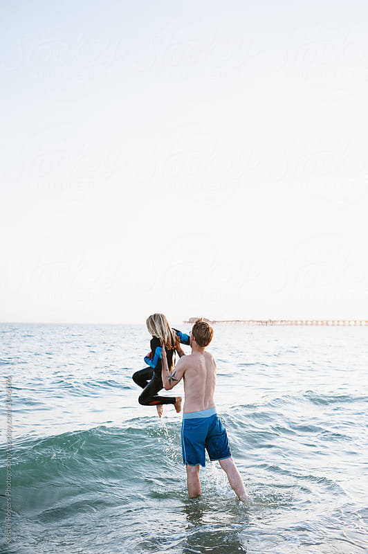 Father throwing daughter for fun in the ocean by Kristin Rogers Photography for Stocksy United