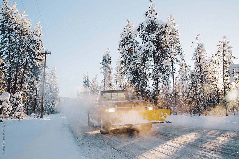 Truck and snowplow on a beautiful day on a snowy road.  by Justin Mullet for Stocksy United