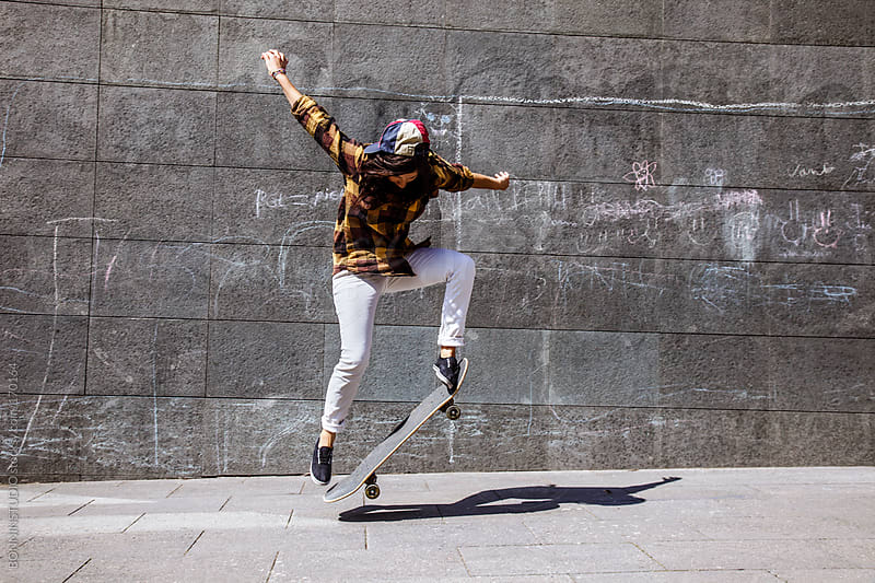 Young skater woman jumping with her skateboard in front dirty wall. by BONNINSTUDIO for Stocksy United