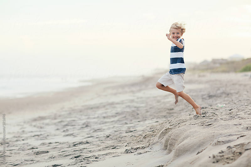 happy boy jumps on the beach by Kelly Knox for Stocksy United