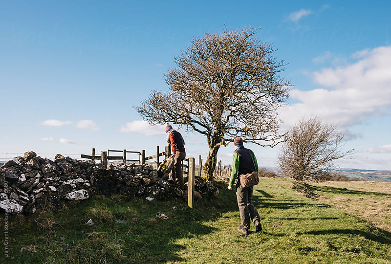 Young couple crossing a wall whilst exploring the countryside. Derbyshire, UK. by Liam Grant for Stocksy United