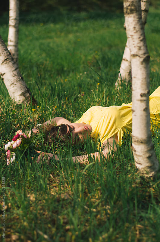 Woman in the yellow dress resting on the grass by Aleksandra Jankovic for Stocksy United