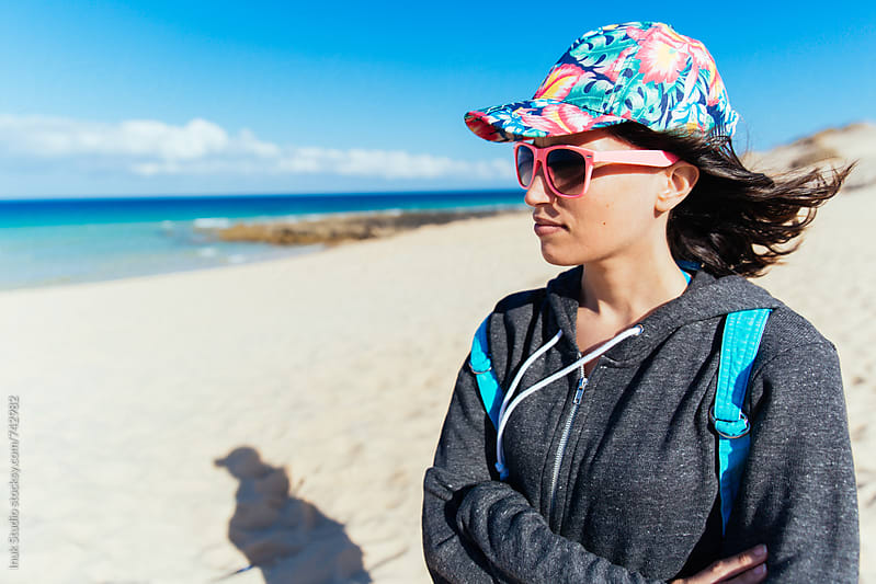 Fashion young woman portrait wearing pink sunglasses and a colourful cap, in a windy beach by Inuk Studio for Stocksy United