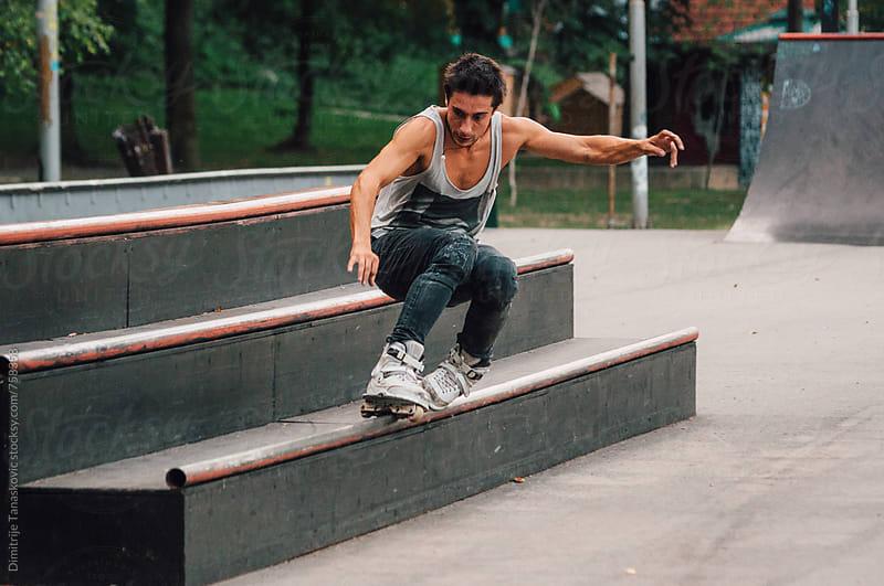 Caucasian man doing trick on his roller blades in skate park by Dimitrije Tanaskovic for Stocksy United