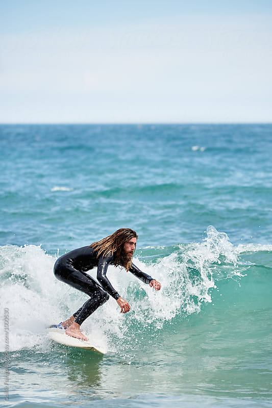 Surfboarder with long hair riding a wave by Guille Faingold for Stocksy United
