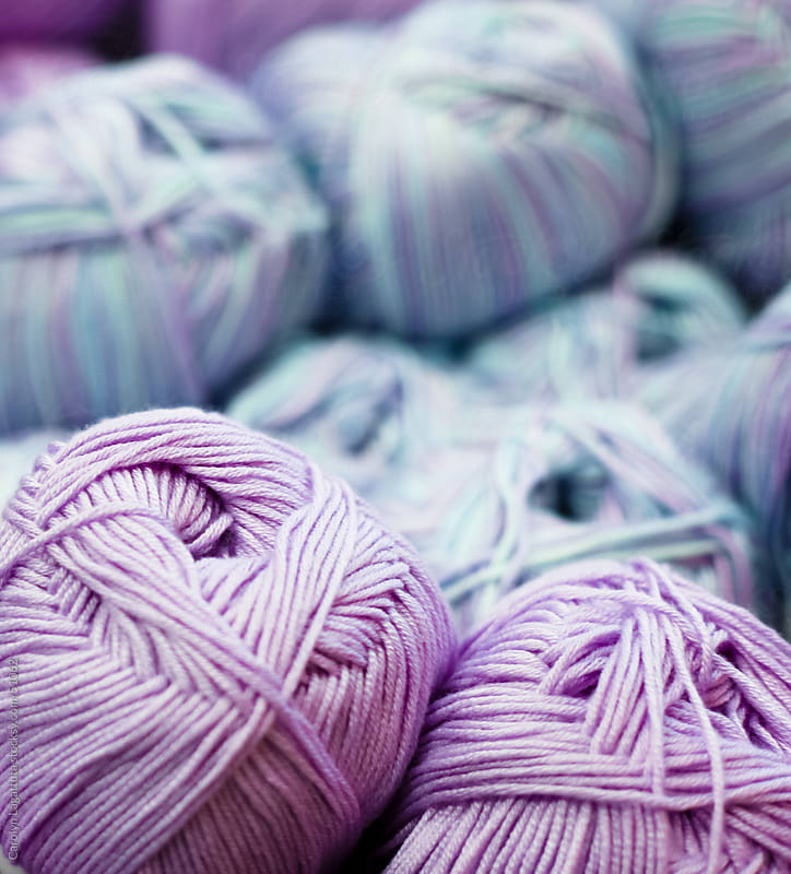 Colorful balls of purople and blue yarn by Carolyn Lagattuta for Stocksy United