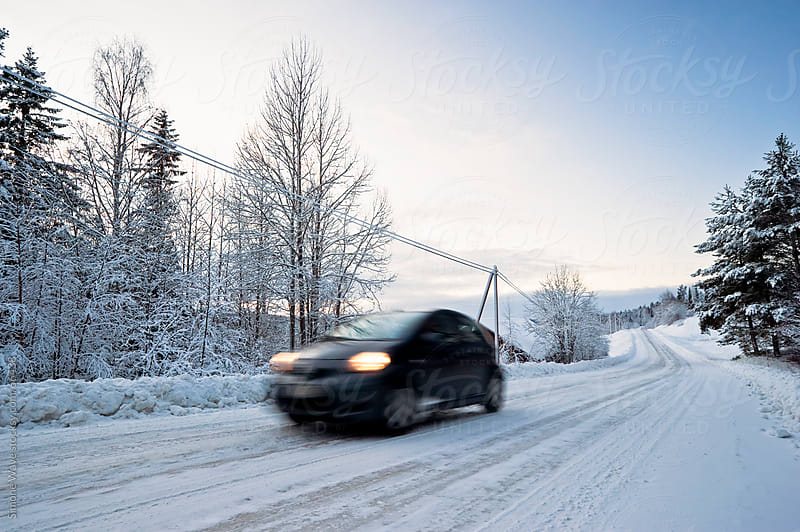 Car driving in a snowy road by GIC for Stocksy United