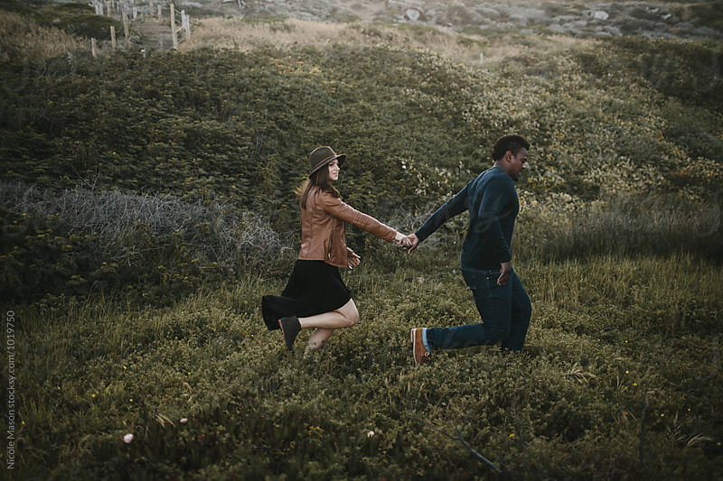 couple running through dark green field at sunrise by Nicole Mason for Stocksy United