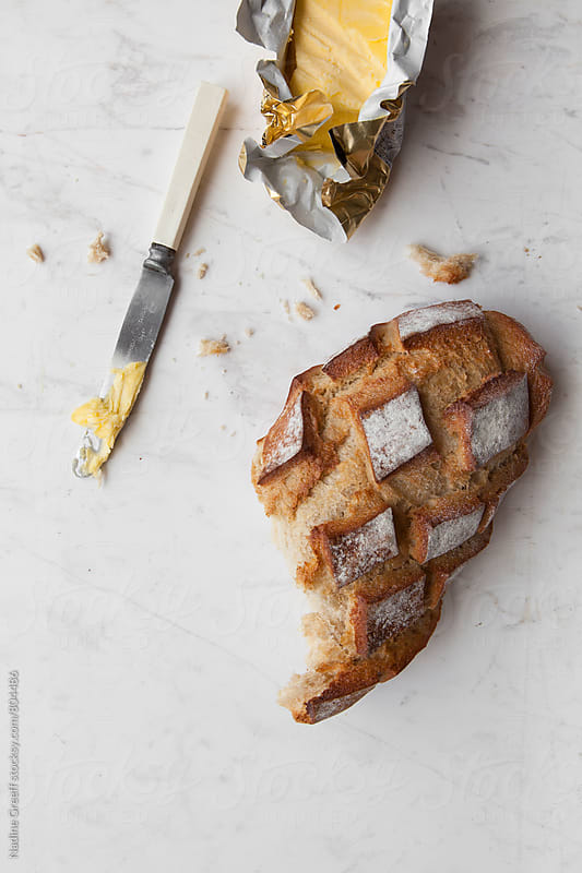 Crusty bread loaf and butter on white background by Nadine Greeff for Stocksy United