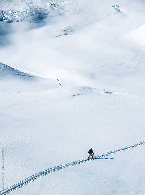 ski tourer on big mountains in a winterlandscape  by Leander Nardin for Stocksy United