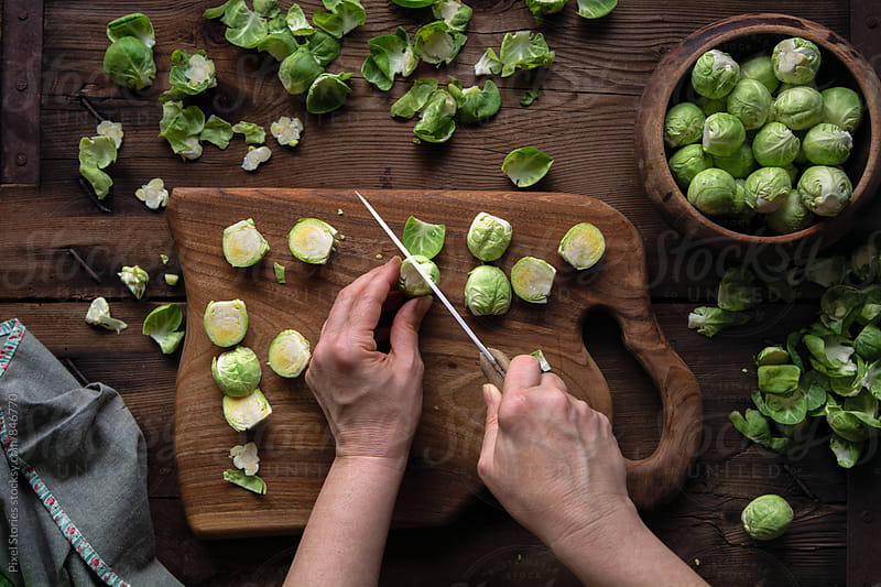 Woman chopping brussel sprouts by Pixel Stories for Stocksy United