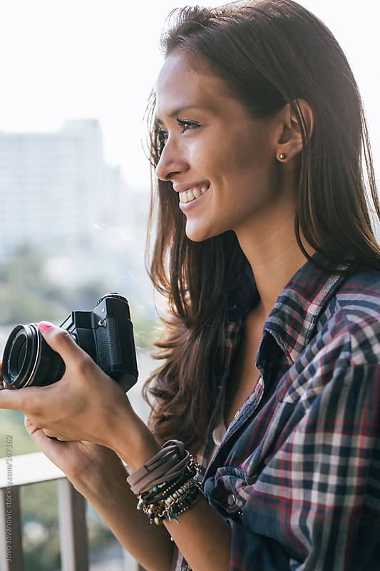 Beautiful woman holding a retro camera and looking at the city. by Jovo Jovanovic for Stocksy United