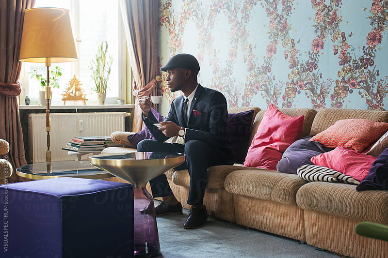 Profile of Elegant Young Black Man Sitting in Bright Living Room and Drinking Espresso by Julien L. Balmer for Stocksy United