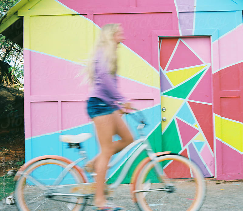 girl on bike against colorful wall by wendy laurel for Stocksy United