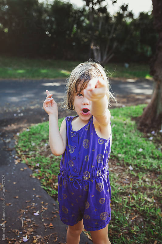Mischievous 4 year old girl with wet hair and purple romper - yelling being goofy by Rob and Julia Campbell for Stocksy United