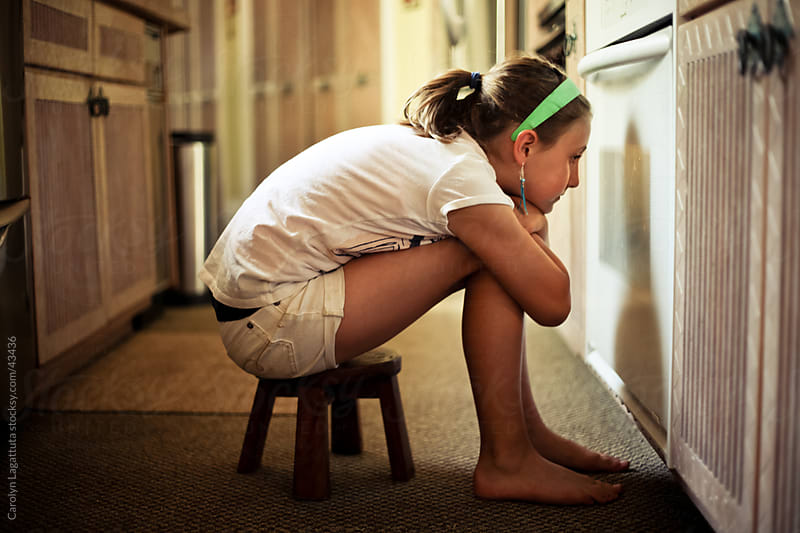 Young woman sitting in front of the oven waiting for what she is baking. by Carolyn Lagattuta for Stocksy United