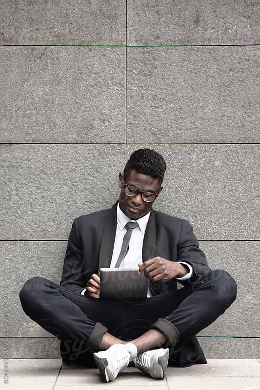 African young businessman sitting on a wall with a tablet by BONNINSTUDIO for Stocksy United