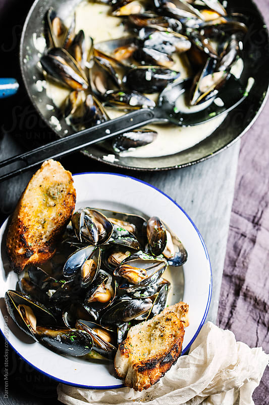 Moules mariniere served in bowl with bread. by Darren Muir for Stocksy United
