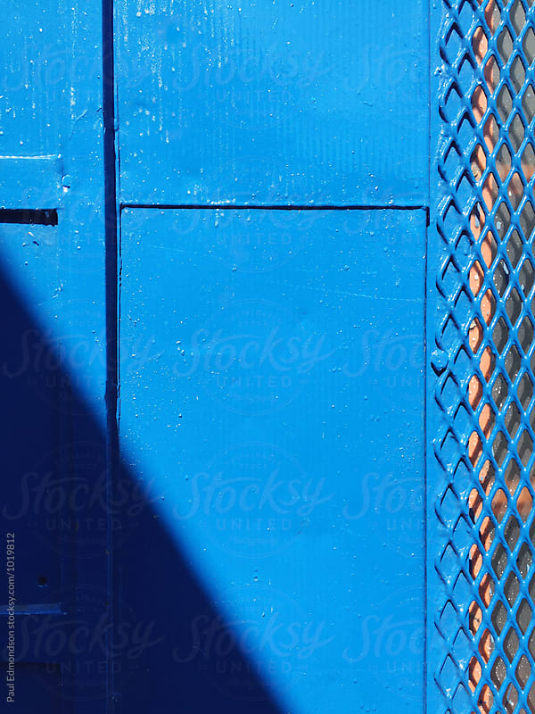 Shadow across painted blue wall, close up by Paul Edmondson for Stocksy United