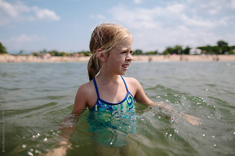 young girl ventures into the lake alone by Brian Powell for Stocksy United