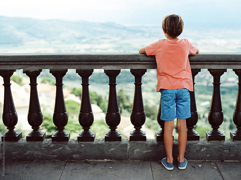 Rear view of boy looking out over balcony in Cortona, Tuscany by Kirstin Mckee for Stocksy United
