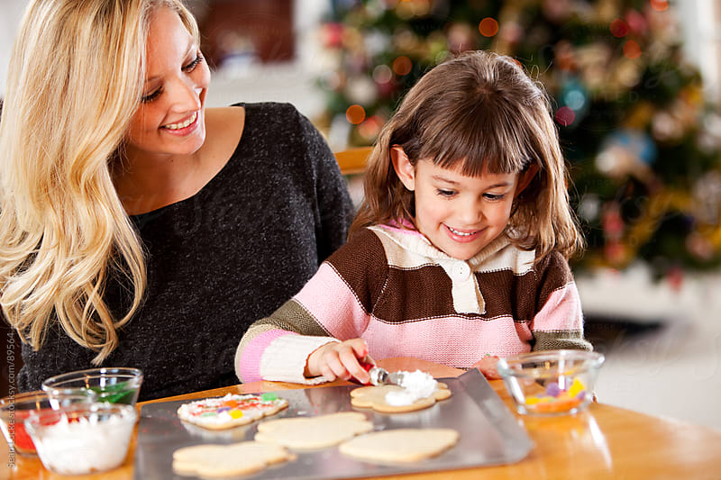 Gingerbread: Daughter Helps to Decorate Cookies by Sean Locke for Stocksy United