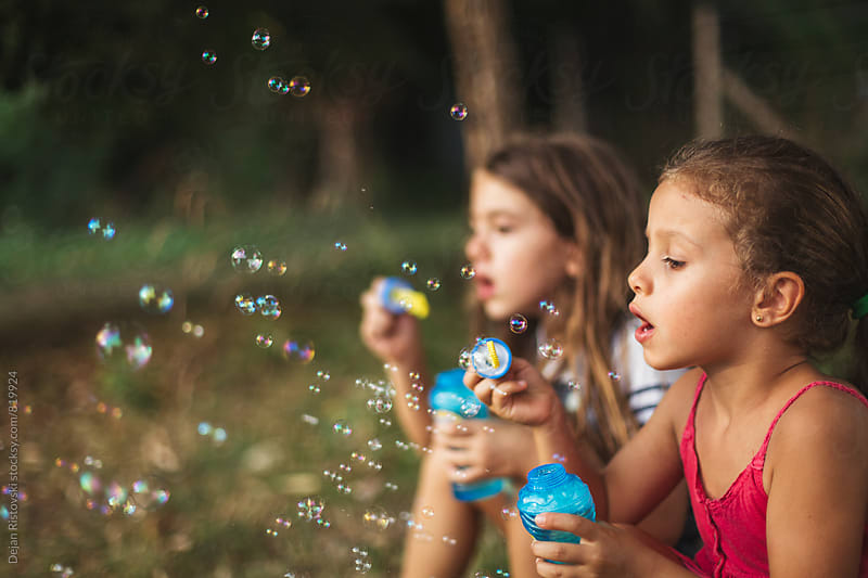 Children blowing bubbles by Dejan Ristovski for Stocksy United