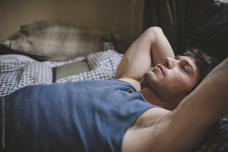 Pensive Man Lying in Bed by Joselito Briones for Stocksy United