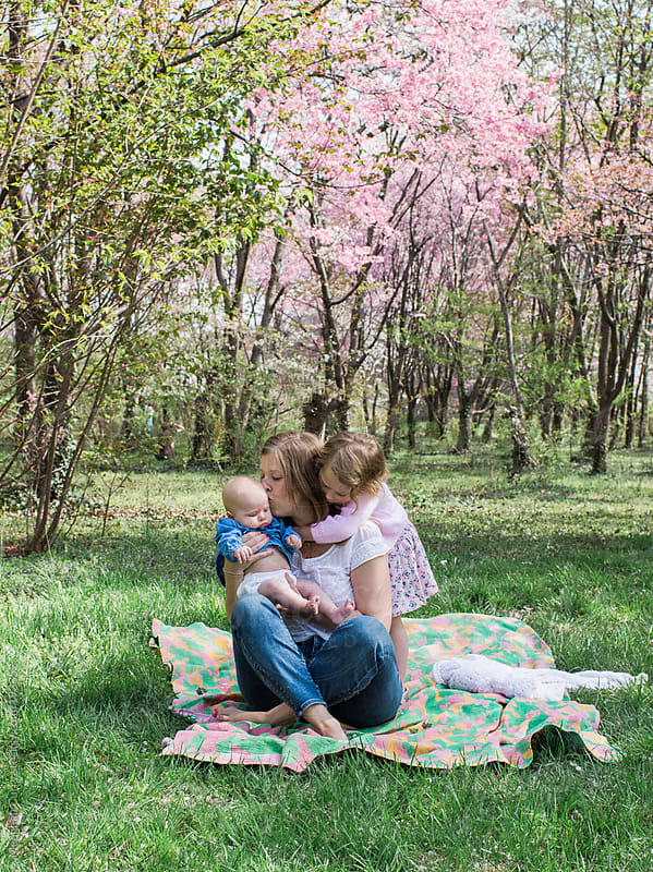 mother and children picnicking under spring blooms by Meaghan Curry for Stocksy United