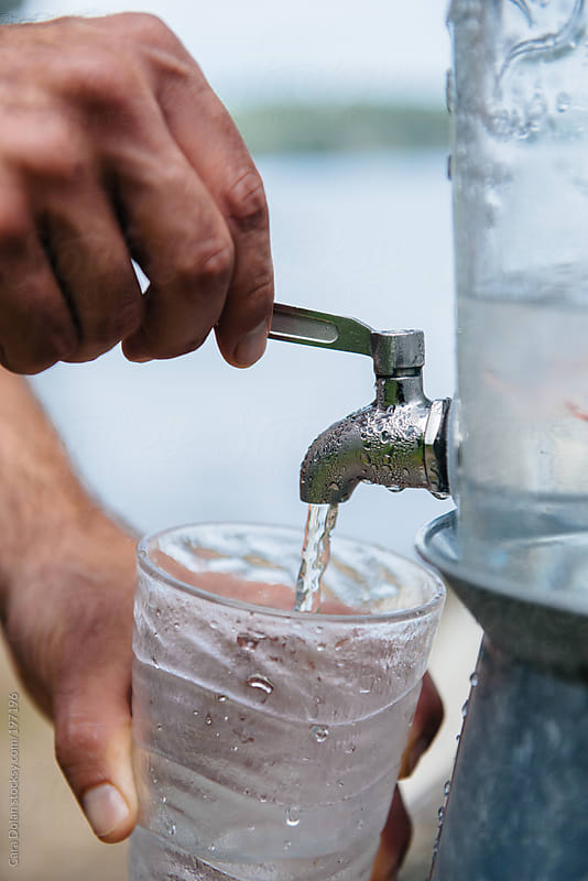 Pouring a drink of ice water from a spout by Cara Dolan for Stocksy United