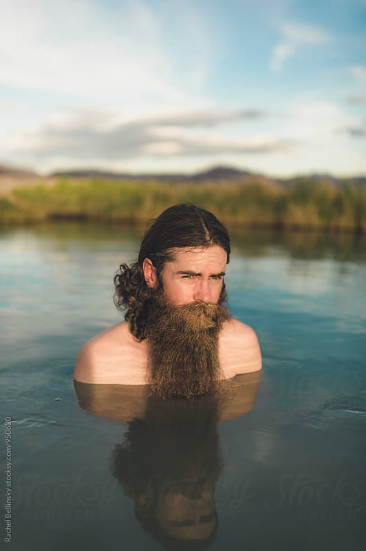 A handsome bearded man in hot springs looks up into the sky by Rachel Bellinsky for Stocksy United