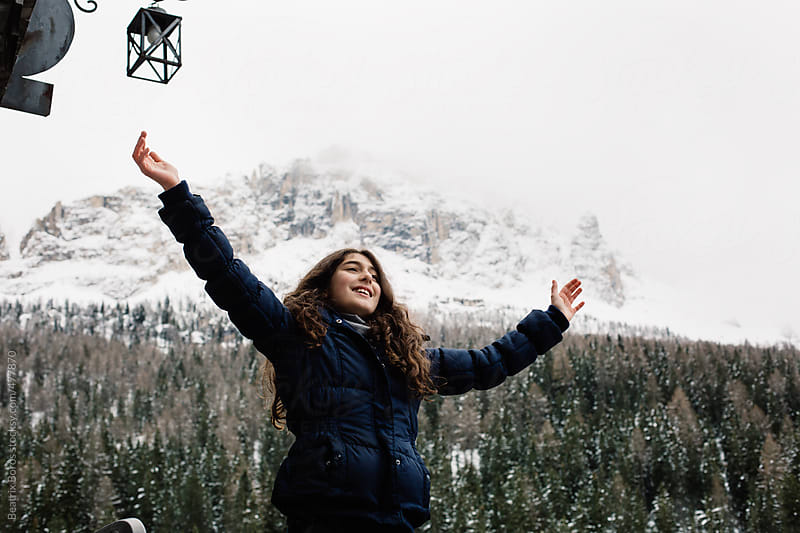 Preteenager girl puts up her hand trimphantly in the winter in front of a mountain by Beatrix Boros for Stocksy United