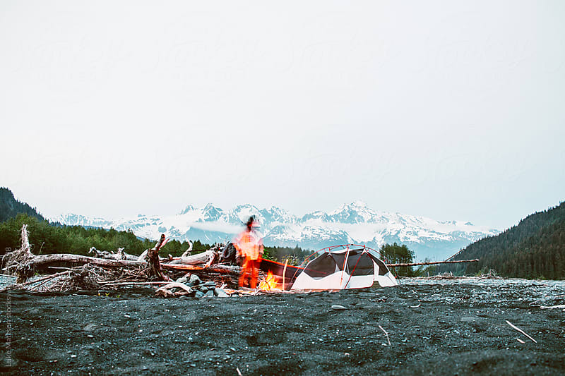 Tending To The Campground Fire At Dusk by Luke Mattson for Stocksy United