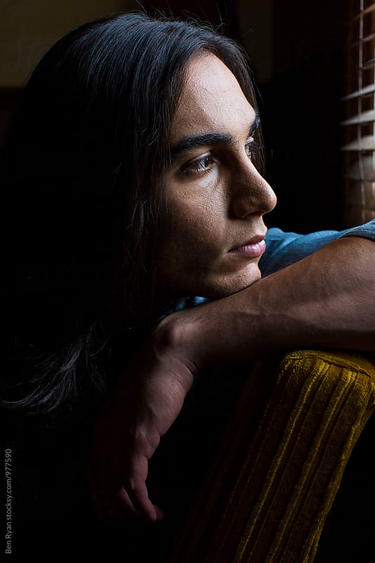 Portrait of young middle eastern man looking out a window by Ben Ryan for Stocksy United
