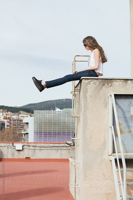 Female teenager sitting on a building rooftop by Miquel Llonch for Stocksy United