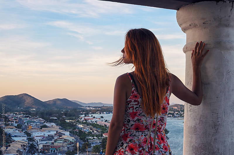 Redhead female overlooking coastal city at the sunset by Alice Nerr for Stocksy United