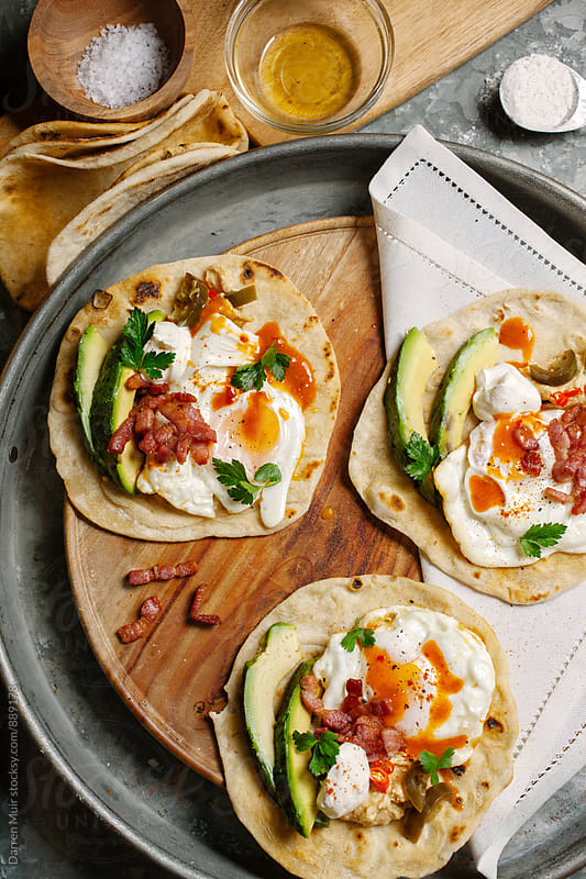 Breakfast tacos overhead view on a wooden serving board. by Darren Muir for Stocksy United