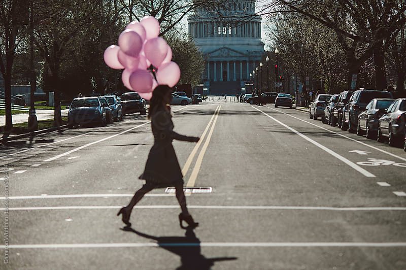 Girl with pink balloons walking around Washignton DC by Cameron Whitman for Stocksy United